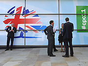 © Licensed to London News Pictures. 03/10/2011. MANCHESTER. UK. Delegates in front of a hoarding bearing the Conservative Party Logo at The Conservative Party Conference at Manchester Central today, October 3, 2011. Photo credit:  Stephen Simpson/LNP