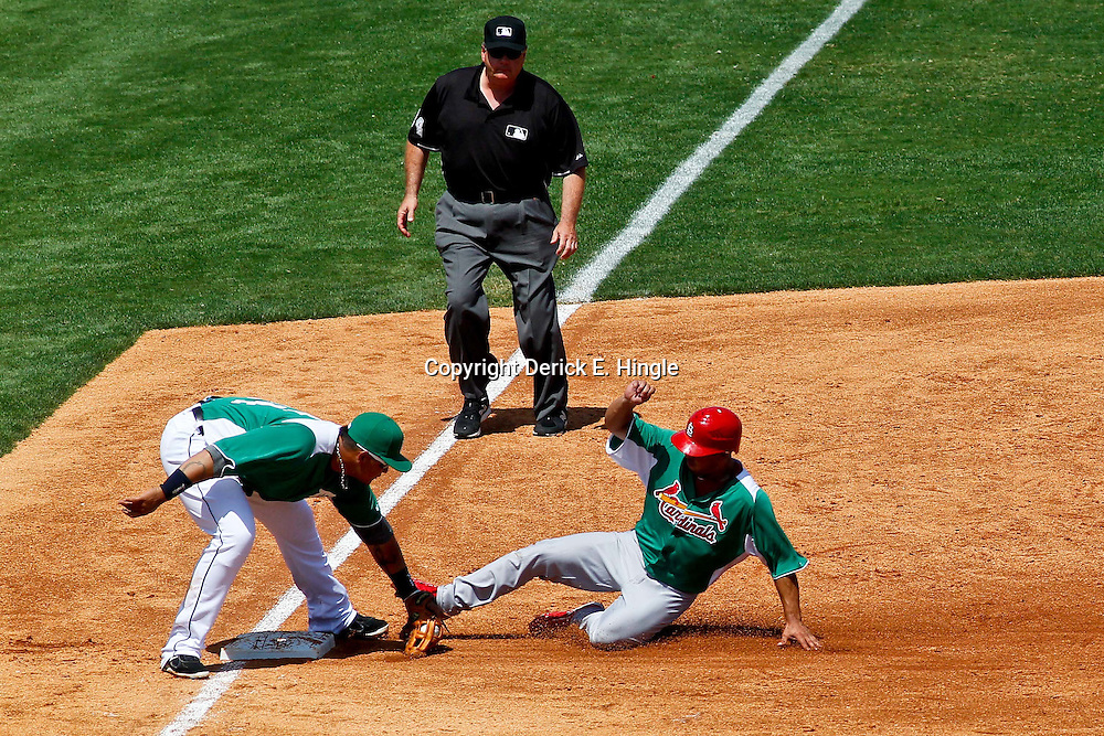 March 17, 2012; Lakeland, FL, USA; St. Louis Cardinals right fielder Erik Komatsu (82) is caught stealing by Detroit Tigers third baseman Miguel Cabrera (24) during the top of the third inning of a spring training game at Joker Marchant Stadium. Both teams wore green jerseys and the field was marked with shamrocks for the St. Patrick's Day game. Mandatory Credit: Derick E. Hingle-US PRESSWIRE