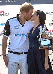 """File photo dated 26/07/18 of the Duke and Duchess of Sussex kissing at the Sentebale ISPS Handa Polo Cup at the Royal County of Berkshire Polo Club in Windsor. The royal couple have announced they are to """"step back"""" as senior members of the royal family and will now divide their time between the UK and North America."""