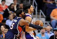 Mar. 1, 2013; Phoenix, AZ, USA; Phoenix Suns forward Luis Scola (14) handles the ball against defender  Atlanta Hawks forward Josh Smith (5) in the first half at US Airways Center. Mandatory Credit: Jennifer Stewart-USA TODAY Sports