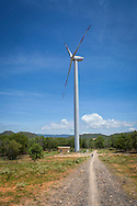 Man walking along a gravel path is dwarfed by a wind turbine on a windfarm in Ninh Thuan Province, Vietnam<br /> , Southeast Asia