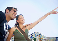 Young couple sitting on stone bench woman pointing into distance portrait