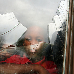 Kyle Green | The Roanoke Times<br /> April 21, 2008 Abdiaziz, age 7, a Somali-Bantu refugee, looks out of a broken window at his parents apartment in the Maple Grove Apartments located at 1141 Pilot Street NW in Roanoke, Virginia. Abdiaziz's family said that the window was broken by a rock thrown by fellow residents of the apartment complex. Tensions between U.S.-reared blacks and African refugees have flared recently, and the police have been to the apartment complex 17 times in March. The Roanoke Refugee and Immigration Services has been placing families from Africa and other countries in area apartments for years, with low rent rates being a key factor in settling them. Maple Grove has been a favored destination for refugees from war-torn Somalia and other African nations, since 2003, said Beth Lutjen, the agency&rsquo;s director. &quot;They have become a community here,&quot; aided by federal rent subsidies and other government financial assistance, she said, walking around the complex on Monday after several complaint calls from her constituents. &quot;But now the tensions between the Africans and the American blacks have reached a crisis point.&quot;