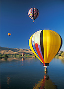 Hot-air balloons over Yakima River during the annual Prosser Balloon Rally & Harvest Festival; Yakima Valley, Washington.