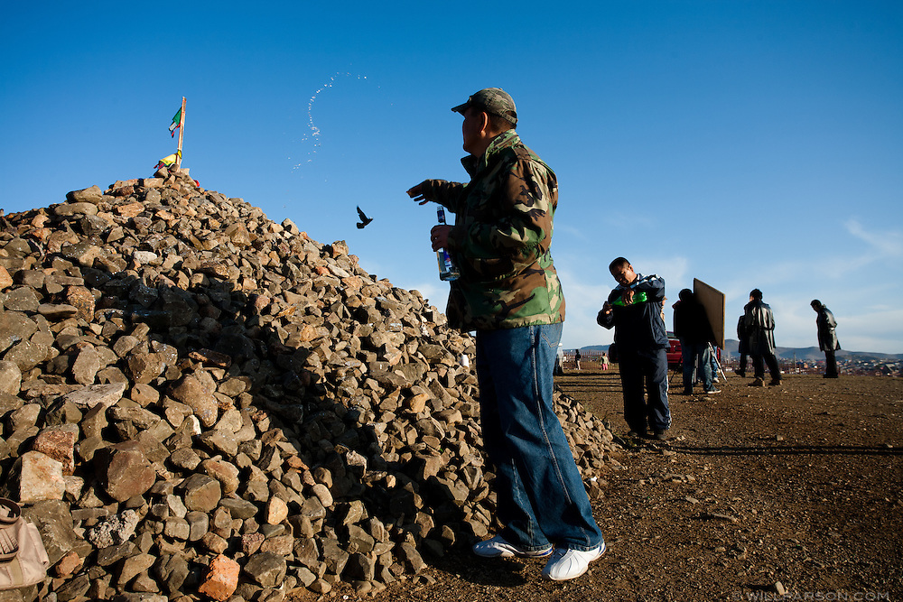 Men pour vodka onto a prayer mound overlooking downtown Ulaanbaatar while nearby a small crew films a Mongolian music video. Ancient shamanistic traditions have persisted in the modern practice of Buddhism in Mongolia.