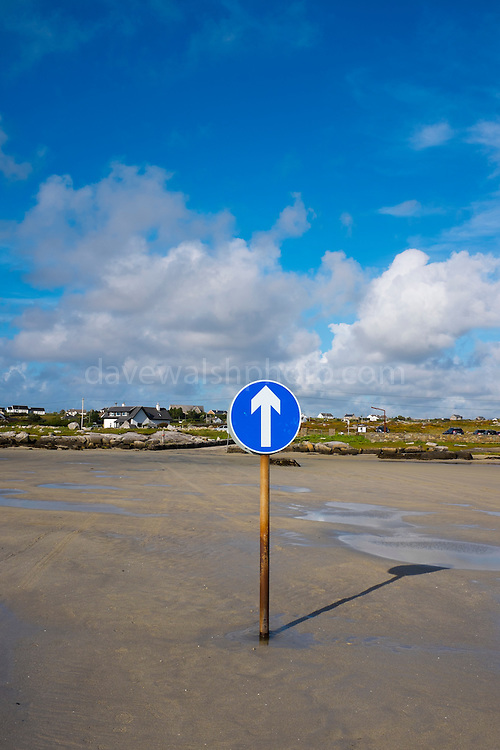 Crossing to Omey Island at low tide, Connemara, Galway, Ireland. Omey is a tidal island - with a signposted route so that can cars can drive out on the sand during low tide.
