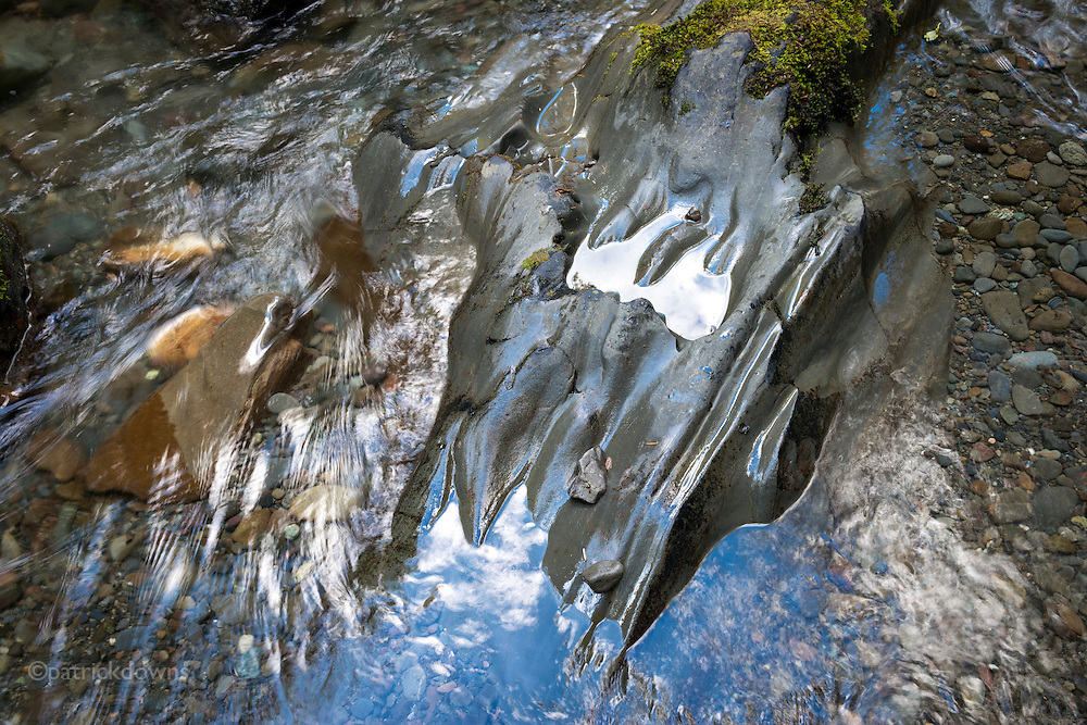 Pools on and around water-sculpted rocks in the upper Dungeness River reflect the sky and clouds above.