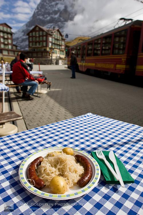 Traditional meal of Bratwurst & saur kraut in view of the Jungfraubahn train and Bellevue des Alpes hotel - Kleine Scheidegg, Switzerland