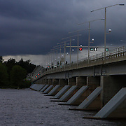 Champlain Bridge crossing Ottawa river and connecting Ottawa, the Capital of Canada and Gatineau, Quebec, August 30, 2009. The photo was taken in the late afternoon with dark clouds rolling out and Quebec style traffic lights on the bridge glowing.