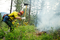 Ricky Skinner, a firefighter with the Idaho Department of Lands, digs a fire line around a small training area set ablaze Thursday on Patzer Peak overlooking Hayden Lake. About 50 firefighters from the area are attending the week-long firefighting guard school hosted by the Coeur d'Alene Interagency Dispatch Center.