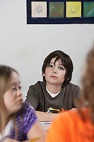 Pensive boy (10-12)  in classroom