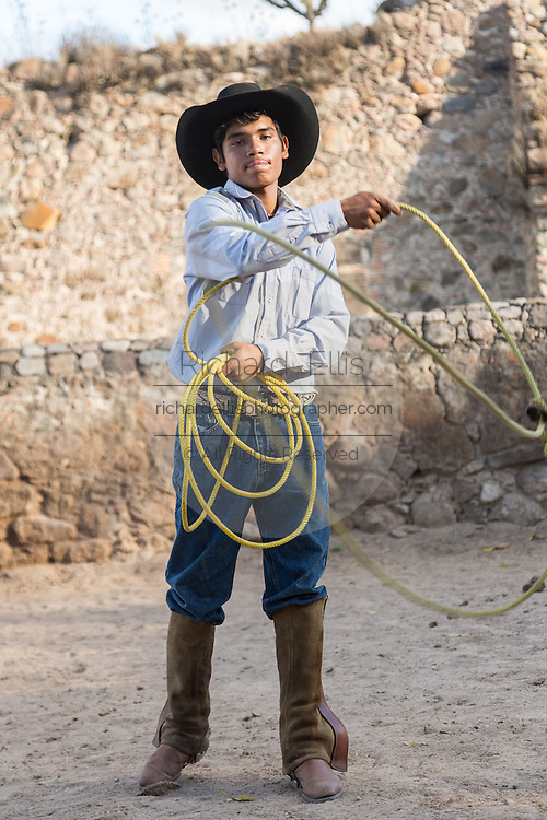 A Mexican charro or cowboy practices roping skills at a hacienda ranch in Alcocer, Mexico. The Charreada is a traditional Mexican form of rodeo and tests the skills of the cowboy at riding, roping and controlling cattle.