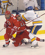 OSU's Cory Schneider (center) takes a hard hit from LSSU's Will Acton (right) that pushes him into the back of teamate Brandon Martell (5) during the first period of the Buckeyes Friday night game against the LSSU Lakers at Taffy Abel Arena in Sault Ste. Marie.