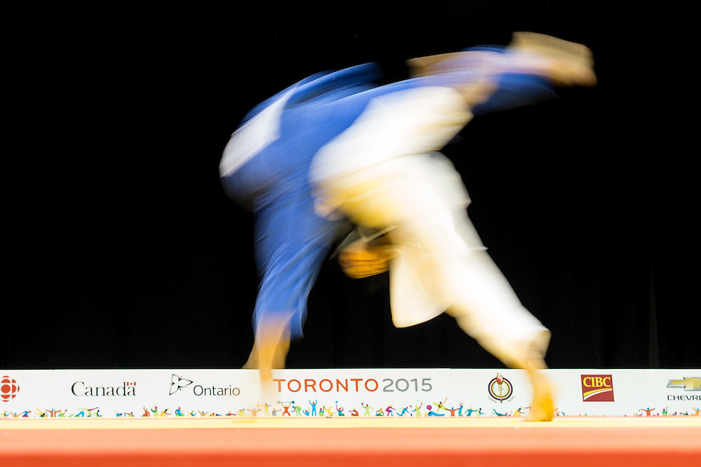 Agusto Miranda (in Blue) of Puerto Rico is thrown by Canada's Arthur Margelidon during their 1/4 final contest in the 73kg class at the 2015 Pan American Games in Toronto, Canada, July 12,  2015.  AFP PHOTO/GEOFF ROBINS