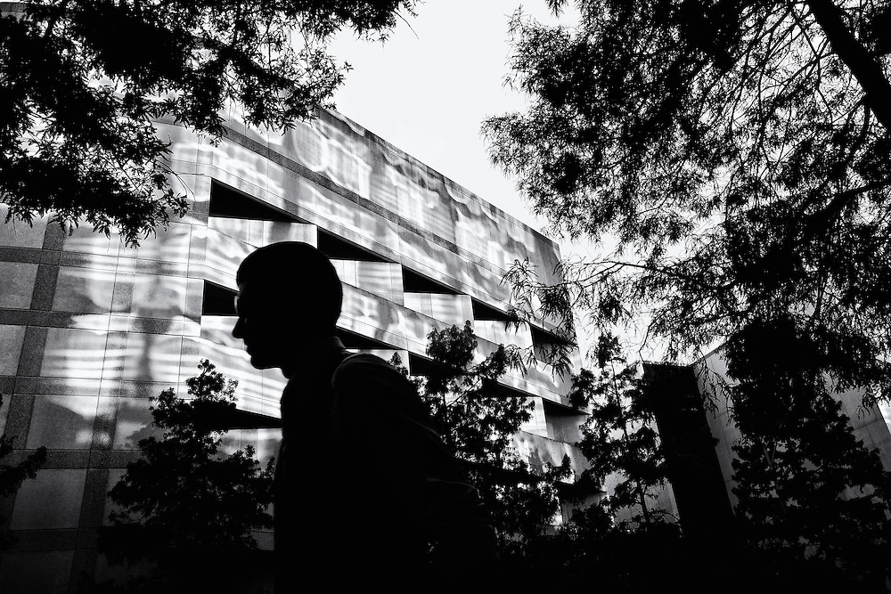 Silhouette of a man in an urban setting with light and shadow striking the building behind him.