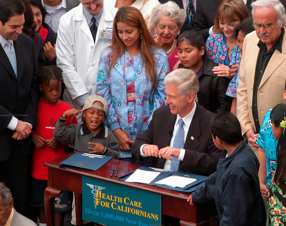 Los Angeles, CA, USA, Oct. 5th 2003: The Governor of California, Gray Davis, signs a new health care plan for California at the Kaiser Permanente Medical Center in West Los Angeles. Supporters of Gray Davis made a point of the Governor dealing with real politics and real life where there's no second take, referring to Arnold Schwarzenegger, who is running against Davis in the California Recall Election.<br /> <br /> Tyler (3) does some flirting with the cameras as he sits next to Mr. Davis<br /> <br /> Photo: Orjan F. Ellingvag/ Dagbladet/ Corbis