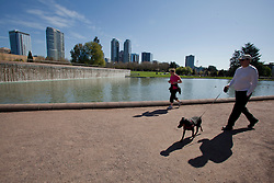 North America, United States, Washington, Bellevue, Bellevue Downtown Park, dog walker and jogger by fountain