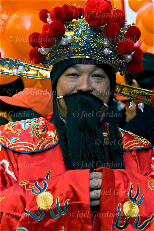 Standing next to parade float close up head and shoulders portrait of Chinese American man wearing tradition folk costume or regalia for the Chinese Lunar New Year Celebration in New York's Chinatown 4706.