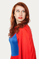 Young woman in superhero costume looking away against gray background