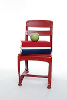 21 July 2008: Children's red school chair with books and a green apple. Back To School on white background.  Red, White, Blue americas education.
