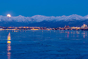 The moon rising from behind the Chugach mountains behind the city lights of Anchorage and an ice Knik Arm in the foreground.