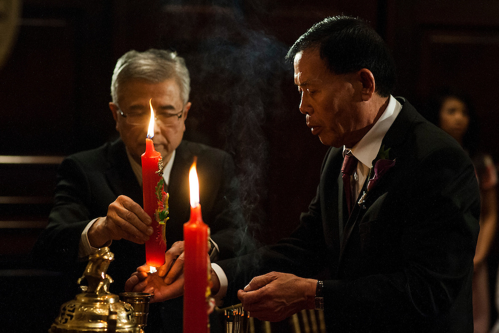 Photo by Matt Roth.Assignment ID: 10137951A..Dr. Tran Trong Gien, left, and Mr. Nguyen Henry Van Hoa, right, fathers of Daniel Tran Gien and Caroline Trang Nguyen light candles during a private traditional Vietnamese tea ceremony at the Carnegie Institution for Science in Washington, D.C. on Saturday, February 02, 2013.