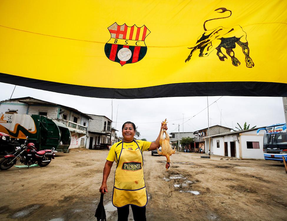 Seg&uacute;n investigaciones antropol&oacute;gicas, hace miles de a&ntilde;os el valle de valdivia fue la cuna de una nueva civilizaci&oacute;n que forjo lo que hoy es sudam&eacute;rica. A pesar de ser uno de los primeros asentamientos humanos en el territorio ecuatoriano, su cultura, en el presente, se preserva en los l&iacute;mites de la modernidad. El trabajo agr&iacute;cola, la pesca y la peque&ntilde;a idustria artesanal y los saberes ancestrales, son el motor de desarrollo de esta regi&oacute;n de la costa ecuatoriana donde su cotidianidad transcurre en creencias de mitos y leyendas como un letargo del pasado. <br /> Foto: Una hincha de Barcelona, el equipo de futbol m&aacute;s popular de Ecuador posa para festejar el triunfo de su equipo mientras lleva un pollo desplumado que ser&aacute; la cena. Adornada con una bandera gigante de su equipo favorito, la principal calle de Valdivia luce vac&iacute;a mientras todos ven el futbol en los televisores de sus casas.