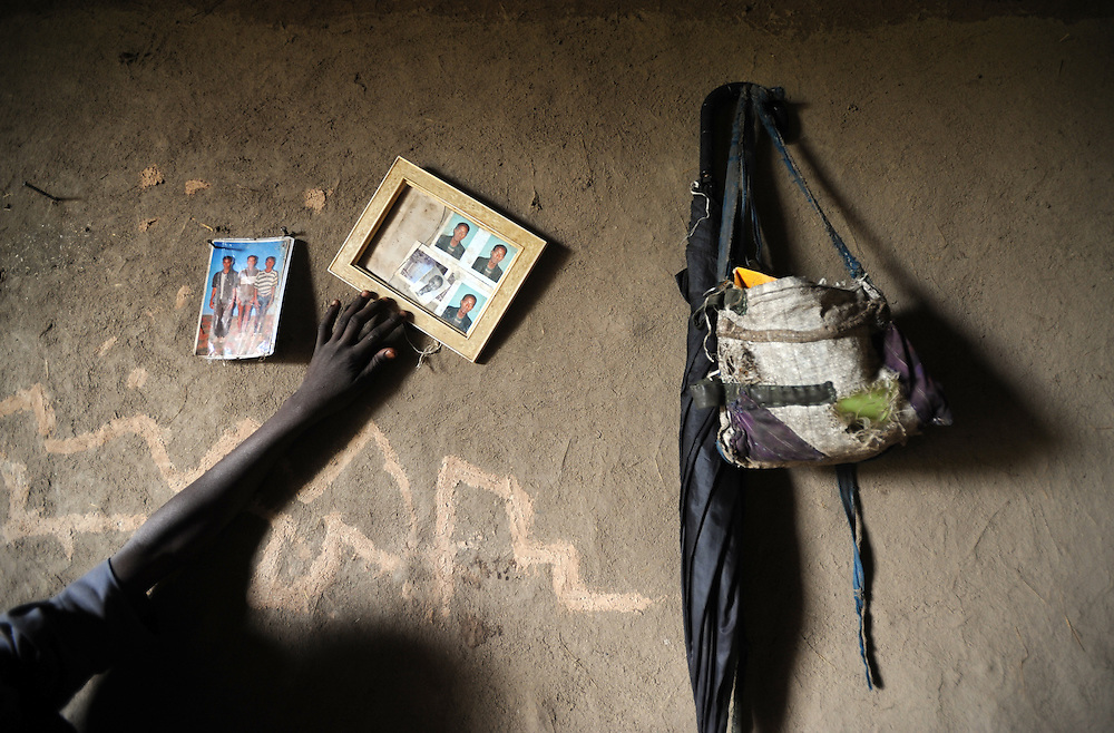 Dronkony (17), who was married at age 6 to Shambel (who was 16) adjusts a photograph of him which is on the wall. They started living together when she was 15 and he was 25.  Ethiopia 8.08.2008