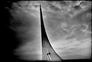 Boys climb space Sputnik monument,  Moscow, Russia.