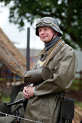 Known by German soldiers of the period as kettenhund or Chain Dogs a reenactor portrays a second world war Field Policeman at the Northallerton Wartime Weekend. He is wearing the classic German Steel Helmet (Stahlhelm) around his neck is a Gasmask canister and his goget. The coat is a waterproof Motorcyclist coat made from rubberised fabric known as a kradmantel <br />