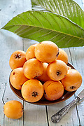 Fresh ripe loquats with leaves on wooden table.