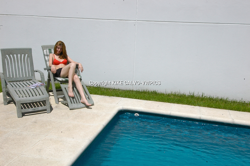 Redhead Argentinian woman in relaxing on a swimming pool