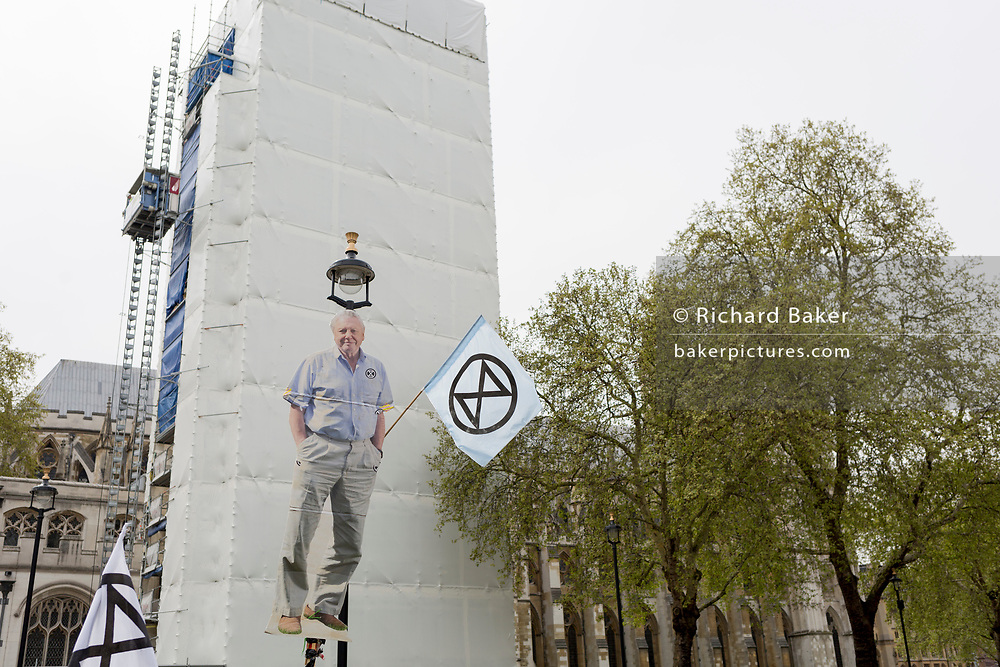 An image of veteran wildlife and environmental broadcaster Sir David Attenborough is held high in Parliament Square during the week-long protest by climate change activists with Extinction Rebellion's campaign to block road junctions and bridges around the capital, on 23rd April 2019, in London England.