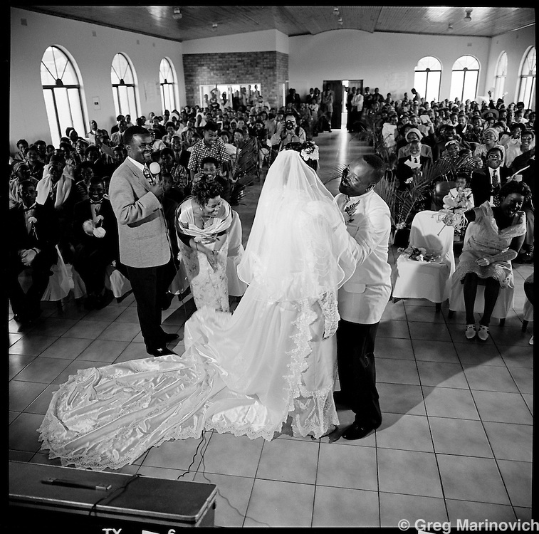 Guava Mthembu marries his bride at the Baptist Church in Esikedwini, northern KwaZulu Natal Nov 7, 1998. Th second half of the marriage was  atraditional Zulu wedding in the strictly Shembe Mthembu household. The founder Isaiah Shembe is seen as a spiritual descendent of Moses and Jesus, and th church embraces traditional Zulu values and customs. Photo Greg Marinovich