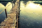 A bamboo bridge stretches across a river in Pai, Thailand