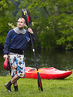 Man with kayak paddle by river