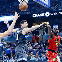 25 February 2017: Atlanta Hawks guard Tim Hardaway Jr. (10) passes the ball around Orlando Magic center Nikola Vucevic (9) and Orlando Magic forward Aaron Gordon (00) during the Orlando Magic 105-86 victory over the Atlanta Hawks, at the Amway Center, Orlando, Florida, USA.