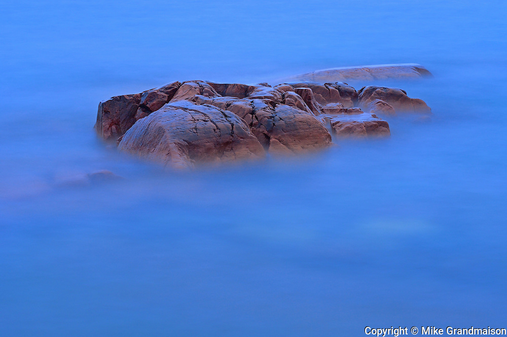 Crashing waves over shorline rocks st dusk<br /> Killarney Provincial PArk<br /> Ontario<br /> Canada