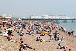 © Licensed to London News Pictures. 12/07/2014. Brighton, UK. People sunbathing on Brighton Beach. With temperatures around the 23C down the South Coast thousands of people taking a weekend away down on the beach. Photo credit : Hugo Michiels/LNP