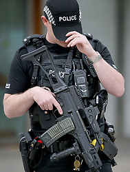 """Armed police on patrol outside the Scottish Parliament building in Holyrood, Edinburgh, after Scotland Yard announced armed troops will be deployed to guard """"key locations"""" such as Buckingham Palace, Downing Street, the Palace of Westminster and embassies."""