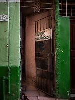 A door with a hand painted sign AGENTE DE TELECOMUNICACION in Havana.
