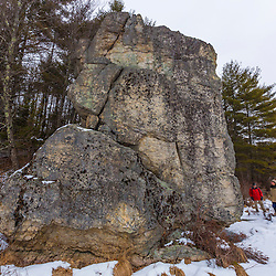 Two men look at a large glacial erratic on the shore of Round Pond in winter. Barrington, New Hampshire.