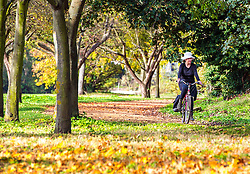 © Licensed to London News Pictures. 31/10/2014. Hampton, UK A woman cycles along the Thames. People enjoy the warm weather at Hampton Court Palace today 31st October 2014. forecasters are predicting It could be the warmest halloween on record. Photo credit : Stephen Simpson/LNP