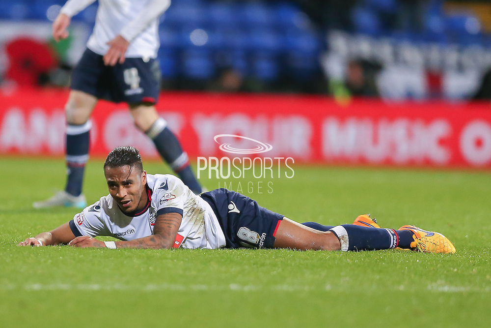 Bolton Wanderers midfielder Neil Danns  lies on the floor after being fouled  during the Sky Bet Championship match between Bolton Wanderers and Brentford at the Macron Stadium, Bolton, England on 30 November 2015. Photo by Simon Davies.