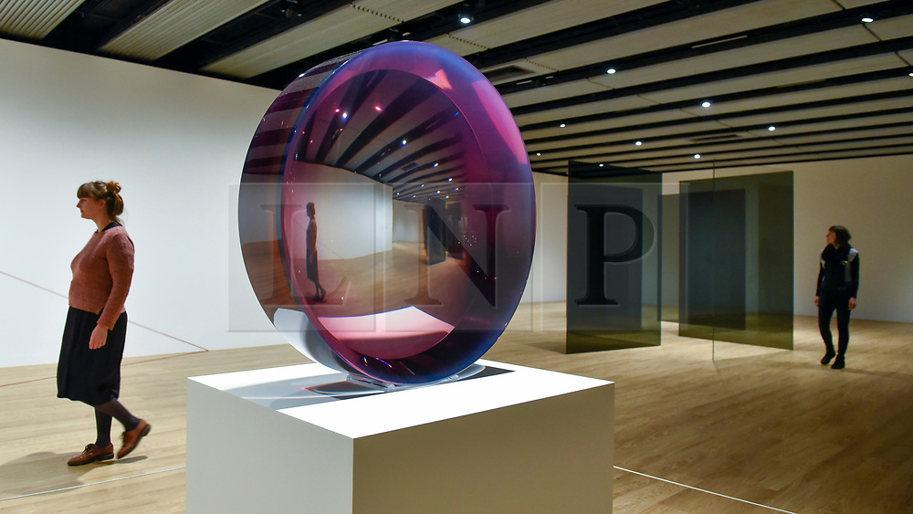 "© Licensed to London News Pictures. 25/09/2018. LONDON, UK. Gallery staff members walk by (L to R) ""Untitled (Parabolic Lens)"", 1971, by Fred Eversley and ""Standing Walls"", 1969/2016 by Larry Bell. Preview of ""Space Shifters"" at the Hayward Gallery, an exhibition which features artworks by 20 leading international artists that disrupt the visitor's sense of space and alter their perception of their surroundings.  The show runs 26 September to 6 January 2019.  Photo credit: Stephen Chung/LNP"