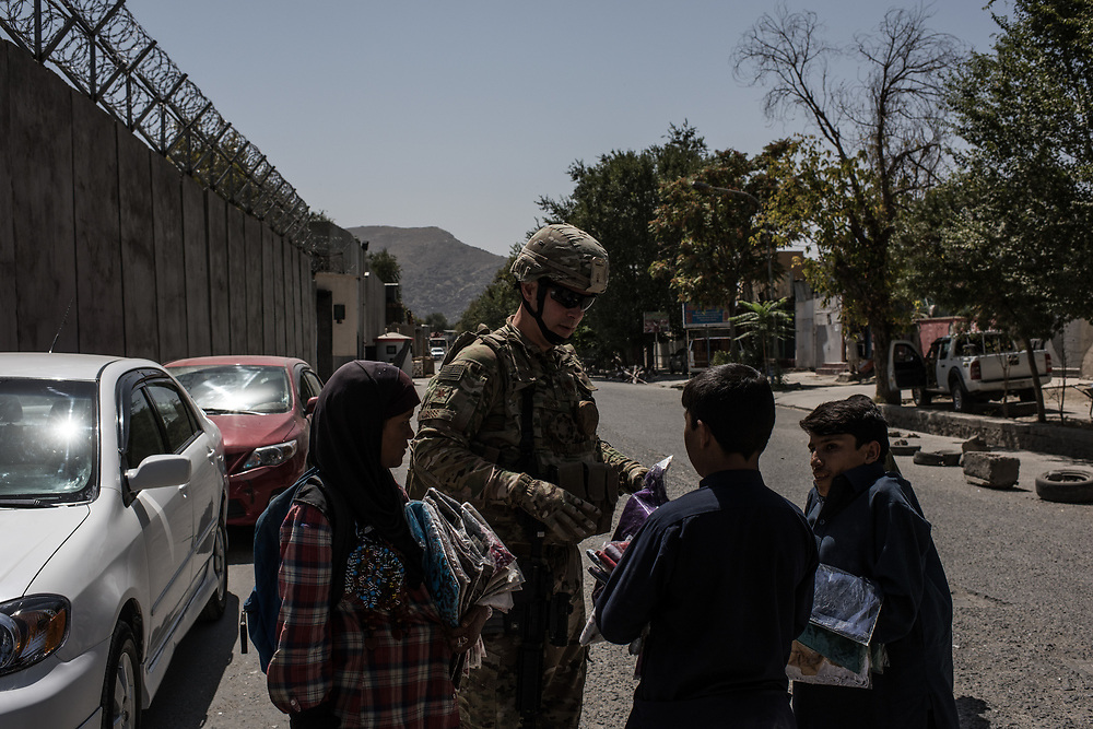 KABUL, AFGHANISTAN - SEPTEMBER 6: United States Air Force Major John Ross buys a scarf for his wife from local Afghans after returning from a public affairs advising mission with the Afghan Ministry of Defense on September 6, 2017 in Kabul, Afghanistan. Currently the United States has about 11,000 troops in the deployed in Afghanistan, with a reported 4,000 more expected to arrive in the coming weeks. Last month, President Donald Trump announced his plan for Afghanistan which called for an increase in troop numbers and a new conditions-based approach to the war, getting rid of a timetable for the withdrawal of American forces in the country. (Photo by Andrew Renneisen/Getty Images)