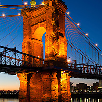 John A. Roebling Suspension bridge tower illuminated at sunset. This bridge spans the Ohio River between Cincinnati Ohio and Covington Kentucky.