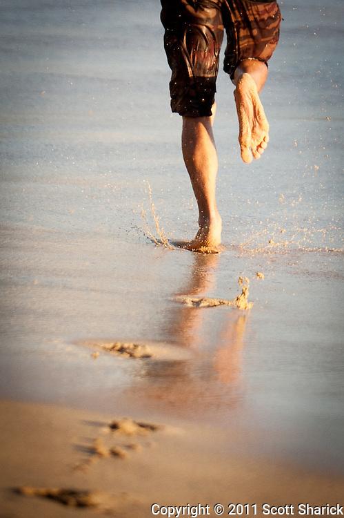 A bodyboarder runs for the shorebreak wave on Waikiki Beach.