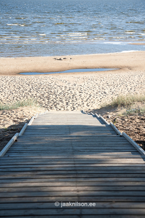 wood deck leading to beach by water