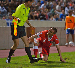 Nicosia, Cyprus - Saturday, October 13, 2007: Wales' captain Craig Bellamy is all smiles after crashing into the assistant referee during the Group D UEFA Euro 2008 Qualifying match against Cyprus at the New GSP Stadium in Nicosia. (Photo by David Rawcliffe/Propaganda)